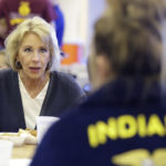 U.S. Secretary of Education Betsy DeVos talks with Gracie Johnsonduring a hog roast before a high school football game between Eastern Hancock and Knightstown, Friday, Sept. 15, 2017, in Charlottesville, Ind. (AP Photo/Darron Cummings)