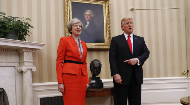 President Donald Trump points to the bust of British Prime Minister Winston Churchill as he poses for photographs with British Prime Minister Theresa May in the Oval Office of the White House in Washington, Friday, Jan. 27, 2017. (AP Photo/Pablo Martinez Monsivais)