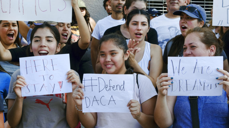 Supporters of the Deferred Action for Childhood Arrivals, or DACA chant slogans and holds signs while joining a Labor Day rally in downtown Los Angeles on Monday, Sept. 4, 2017. (AP Photo/Richard Vogel)