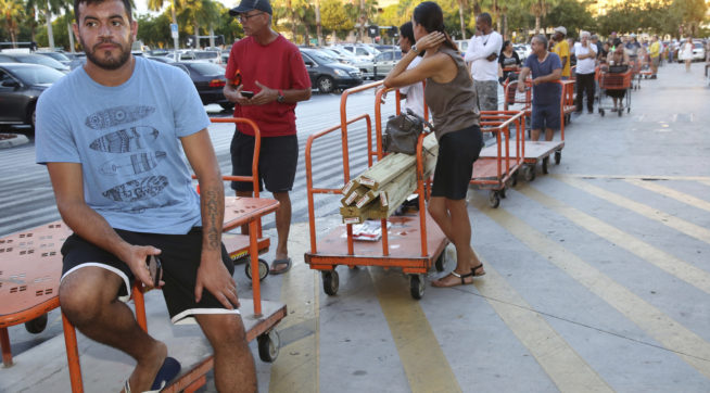 Max Garcia of Miami, waits in a line since dawn to purchase plywood sheets at a Home Depot store in North Miami, Fla., Wednesday Sept. 6, 2017. Florida residents are preparing for the possible landfall of Hurricane Irma, the most powerful Atlantic Ocean hurricane in recorded history. (AP Photo/Marta Lavandier)