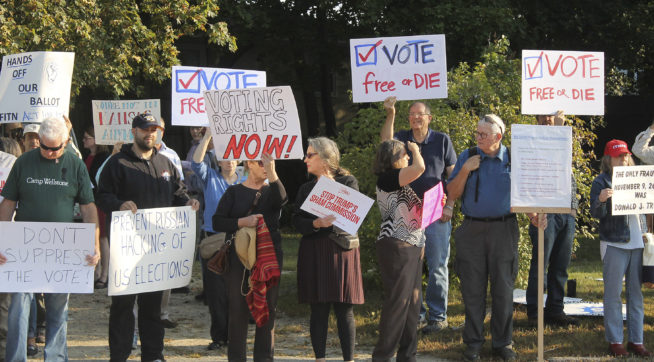 "Protesters gather on Tuesday, Sept. 12, 2017, at Saint Anselm College in Manchester, New Hampshire, ahead of a  day-long meeting of the Trump administration's election integrity commission. They argue the commission, which is tasked with investigating voter fraud, is a sham. Signs reading ""Vote Free or Die"" played off New Hampshire's motto: ""Live Free or Die."" (AP Photo/Holly Ramer)."