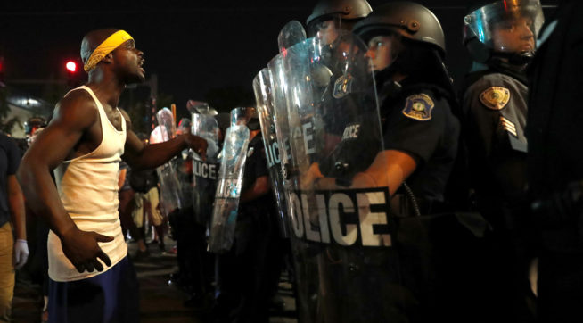 A man yells at police in riot gear just before a crowd turned violent Saturday, Sept. 16, 2017, in University City, Mo. Earlier, protesters marched peacefully in response to a not guilty verdict in the trial of former St. Louis police officer Jason Stockley . (AP Photo/Jeff Roberson)