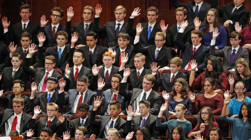 Members of a youth choir raise their hands during a sustaining vote during the afternoon session of the two-day Mormon church conference Saturday, Sept. 30, 2017, in Salt Lake City.  (AP Photo/Rick Bowmer)