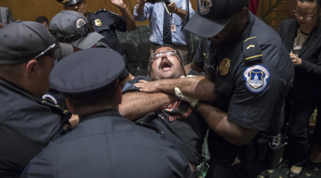 Activists opposed to the  GOP's Graham-Cassidy health care repeal bill, many with disabilities, are removed by U.S. Capitol Police after disrupting a Senate Finance Committee hearing on the last-ditch GOP push to overhaul the nation's health care system, on Capitol Hill in Washington, Monday, Sept. 25, 2017. (AP Photo/J. Scott Applewhite)