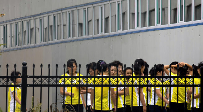 In this Sept. 5, 2017, photo, North Korean workers gather after lunch at the Hong Chao Zhi Yi garment factory in Hunchun in northeastern China's Jilin province. At a time when North Korea faces sanctions on many exports, the outsourcing of tens of thousands of workers worldwide brings in revenue estimated at anywhere from $200 million to $500 million. That could account for a sizable portion of its nuclear weapons and missile programs, which South Korea says has cost well over $1 billion. (AP Photo/Ng Han Guan)