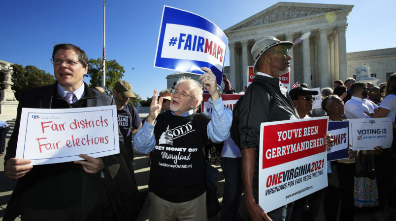 Eric Silberman from Silver Spring, Md., from left,Charlie Cooper from Baltimore, Md., and Clay Wilson from Alexandria, Va., join others in a rally for a fair election outside the U.S. Supreme Court in Washington, Tuesday, Oct. 3, 2017. The Supreme Court hears arguments in a case about political maps in Wisconsin that could affect elections across the country. (AP Photo/Manuel Balce Ceneta)