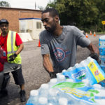 "Shawn Jones, 42, right, and Tony Price, 54, distribute bottled water at a point of distribution (POD) at Saint Mark Missionary Baptist Church on Friday, August 11, 2017, in Flint's Second Ward. The POD closes today. Jones, who's been driving pallets of water to the site since November, said he hasn't seen demand slacken. He worries that as PODs close in Flint over the next month, city residents will crowd those that remain open. ""I don't see this ending,"" he said. ""It's going to be hectic."" Asserting that Flint's water is now generally safe to drink, state and city officials have begun to reduce the number of bottled water points of distribution, or PODs, in the city. The closures begin today with two sites, one in the Second Ward and another in the Third. On September 5, three more will close, in the Fifth, Seventh and Eighth wards respectively. A total of four PODs, located in the First, Fourth, Sixth and Ninth wards, are slated to remain open indefinitely. Terray Sylvester 
