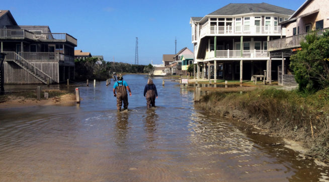 /// A couple walks along a road flooded with sea water brought by Hurricane Maria's waves in Buxton, North Carolina, on Wednesday Sept. 27th, 2017. The storm continues to linger off the coast of North Carolina, lashing the Outer Banks with a wind-driven storm surge that is eroding beaches and washing over Hatteras and Ocracoke. (AP Photo/Ben Finley)
