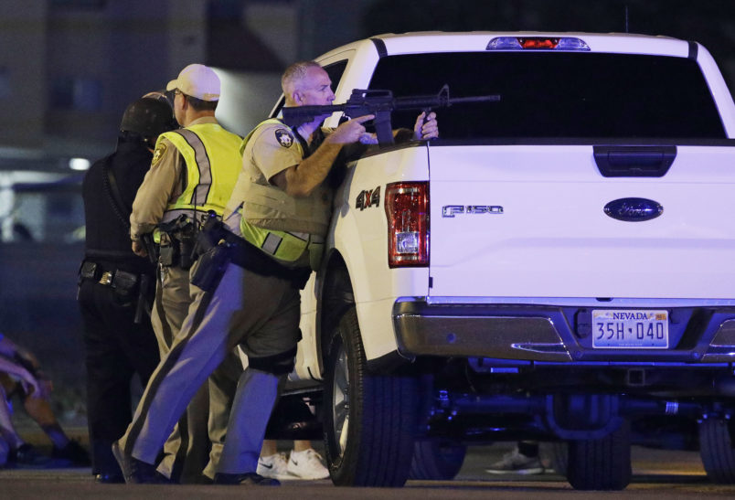 A police officer takes cover behind a truck at the scene of a shooting near the Mandalay Bay resort and casino on the Las Vegas Strip, Sunday, Oct. 1, 2017, in Las Vegas. (AP Photo/John Locher)