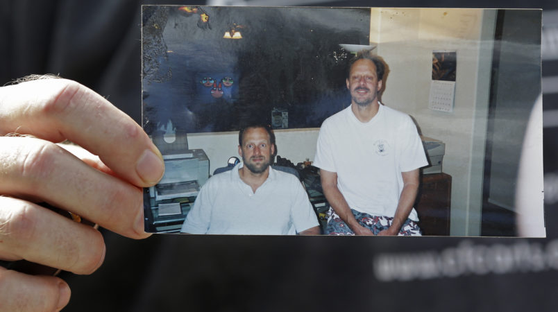 Eric Paddock, brother of  Las Vegas gunman Stephen Craig Paddock, holds up a photo of he and his brother outside his home, Monday, Oct. 2, 2017, in Orlando, Fla. Eric Paddock is on the left. (AP Photo/John Raoux)