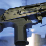 """A little-known device called a """"bump stock"""" is attached to a semi-automatic rifle at the Gun Vault store and shooting range Wednesday, Oct. 4, 2017, in South Jordan, Utah. (AP Photo/Rick Bowmer)"""