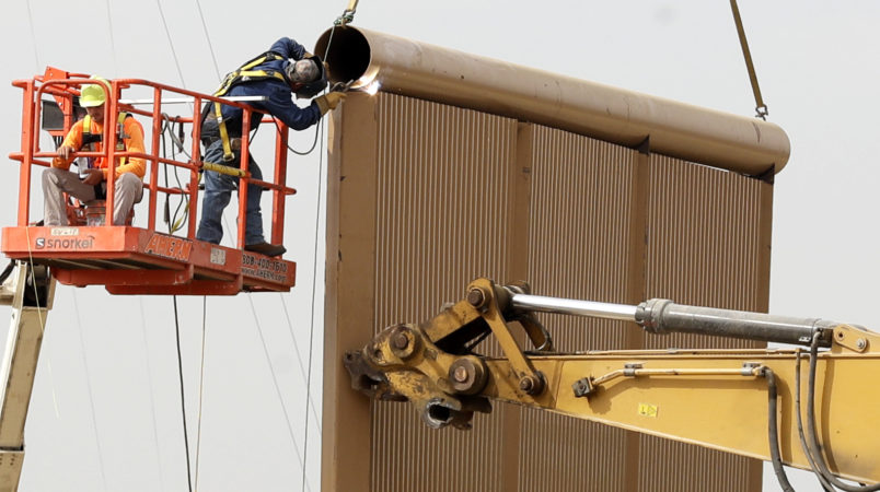 """Crews work on a border wall prototype near the border with Tijuana, Mexico, Thursday, Oct. 19, 2017, in San Diego. Companies are nearing an Oct. 26 deadline to finish building eight prototypes of President Donald Trump's proposed border wall with Mexico. The models, which cost the government up to about $500,000 each, should be able to take an hour of punishment from a sledgehammer, pickaxe, torch, chisel and battery-operated tools and be """"aesthetically pleasing"""" from the U.S. side. (AP Photo/Gregory Bull)"""