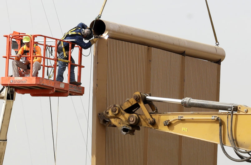 "Crews work on a border wall prototype near the border with Tijuana, Mexico, Thursday, Oct. 19, 2017, in San Diego. Companies are nearing an Oct. 26 deadline to finish building eight prototypes of President Donald Trump's proposed border wall with Mexico. The models, which cost the government up to about $500,000 each, should be able to take an hour of punishment from a sledgehammer, pickaxe, torch, chisel and battery-operated tools and be ""aesthetically pleasing"" from the U.S. side. (AP Photo/Gregory Bull)"