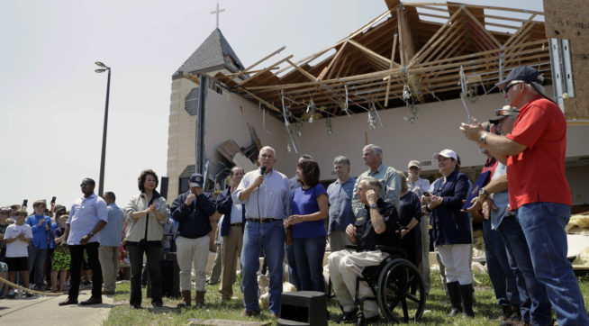 MOVE AT 9:00 AM EASTERN TUESDAY NOV. 7 - FILE - in this Aug. 31, 2017 file photo, Vice President Mike Pence,with his wife Karen, speak to residents affected by Hurricane Harvey during a visit to the First Baptist Church, in Rockport, Texas. The church, which was hit by Harvey, has not filed a lawsuit against the Federal Emergency Management Agency, challenging the agency's policy of denying disaster aid to repair or rebuild places of worship as others have. When disaster strikes, religious institutions like churches and synagogues often form a community's front line of response while working alongside the Federal Emergency Management Agency. Places of worship are routinely denied FEMA aid when it comes time to repair and rebuild their own damaged sanctuaries. (AP Photo/Eric Gay File)