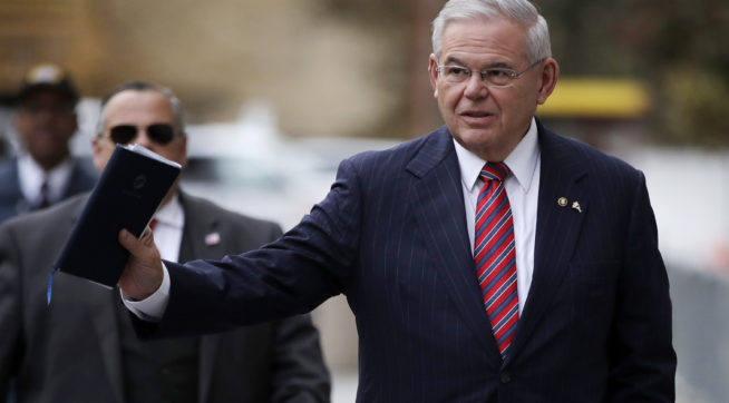 U.S. Sen. Bob Menendez waves at reporters before entering the Martin Luther King Jr. Federal Courthouse for his federal corruption trial, Thursday, Nov. 16, 2017, in Newark, N.J. Jury deliberations continued on Thursday morning. (AP Photo/Julio Cortez)
