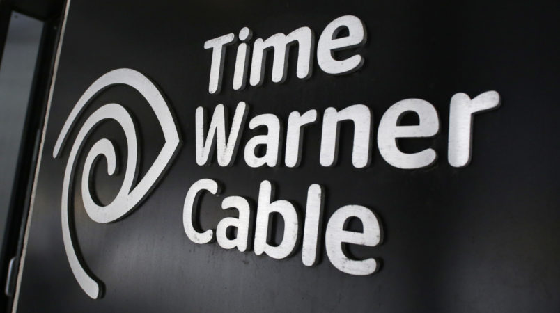 FILE - In this May 26, 2015, file photo, the Time Warner Cable corporate logo is displayed at a company store, in New York. On Monday, April 25, 2016, the Justice Department approved Charter's bid to buy Time Warner Cable and create another cable giant. Monday's OK comes with conditions meant to preserve competition from online services. Additional approvals are required, but expected, before the deal closes. (AP Photo/Mark Lennihan, File)