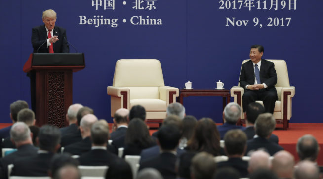 U.S. President Donald Trump speaks next to Chinese President Xi Jinping on stage during a business event at the Great Hall of the People in Beijing, Thursday, Nov. 9, 2017. Trump is on a five-country trip through Asia traveling to Japan, South Korea, China, Vietnam and the Philippines. (AP Photo/Andy Wong)