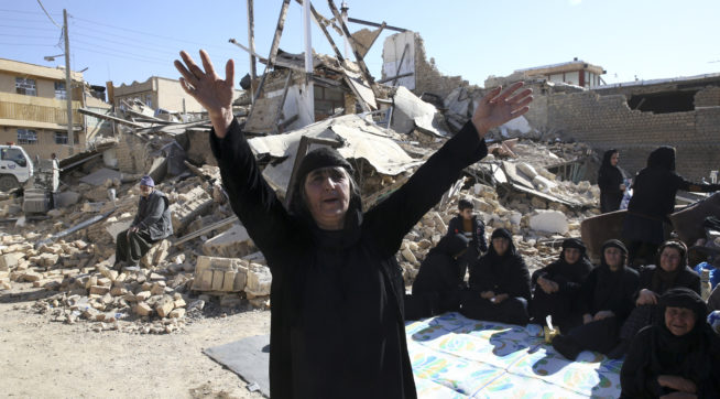 A woman moans on the earthquake site in Sarpol-e-Zahab in western Iran, Tuesday, Nov. 14, 2017. Rescuers are digging through the debris of buildings felled by the Sunday earthquake that killed more than four hundred people in the border region of Iran and Iraq. (AP Photo/Vahid Salemi)