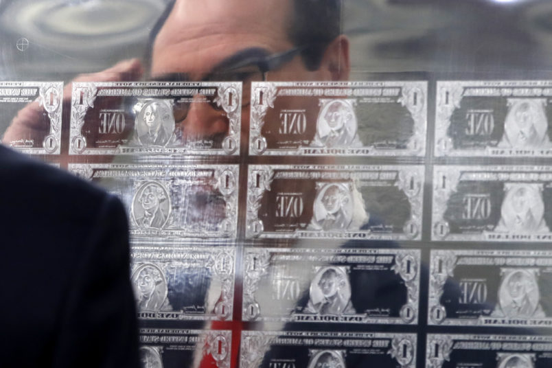 Treasury Secretary Steven Mnuchin is reflected in a printing plate of $1 notes bearing his signature, Wednesday, Nov. 15, 2017, at the Bureau of Engraving and Printing in Washington. The new series of 2017, 50-subject $1 notes, will be sent to the Federal Reserve to issue into circulation. (AP Photo/Jacquelyn Martin)