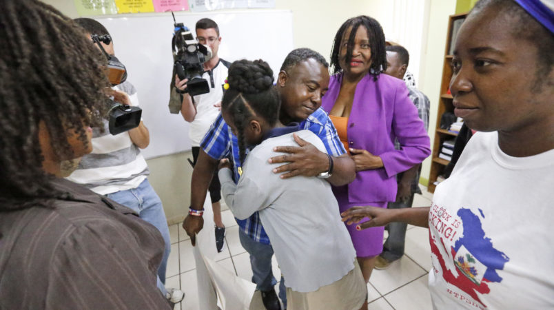 Pierrot Mervilier, center rear, hugs a girl that did not wish to be identified, living in the U.S. with Temporary Protected Status (TPS) after she and her family spoke to members of the media, Monday, May 22, 2017, in Miami. The Trump administration is going to extend humanitarian protections for tens of thousands of Haitian immigrants who have been living in the United States since a deadly earthquake. Administration officials said the TPS for roughly 50,000 Haitians will expire in December. A final decision about the long-term fate of those immigrants will be decided at a later date. (AP Photo/Wilfredo Lee)