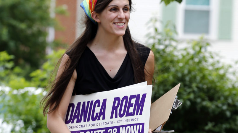 Democratic nominee for the House of Delegates 13th district seat, Danica Roem, brings campaign signs as she greets voters while canvasing a neighborhood Wednesday, June 21, 2017, in Manassas, Va. Roem is running against Del. Bob Marshall in the 13th House of Delegates District. (AP Photo/Steve Helber)
