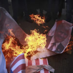 Palestinian protesters burn a poster of U.S. President Donald Trump and mocks of Israeli and American flags, during a protest against US decision to recognize Jerusalem as Israel's capital, in Gaza City Thursday, Dec. 7, 2017. (AP Photo/ Khalil Hamra)