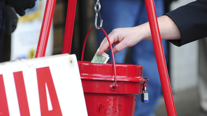 A patron donates money as the The Salvation Army of Wilkes-Barre celebrated its season of generosity with its annual Red Kettle Kick-Off, Wednesday, November 22, at Schiel's Market on Hanover Street in Wilkes-Barre, Pa., The iconic tradition of bell ringers and red kettles is the most recognizable fundraising effort for The Salvation Army. Mark Morancv23salvationp1PAWIC101