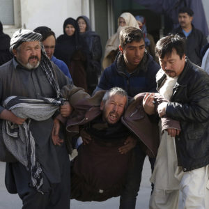 An Afghan man, center, cry after after a suicide attack in Kabul, Afghanistan, Thursday, Dec. 28, 2017. Authorities say two simultaneous attacks, including a suicide bombing attack, in Afghanistan's capital have left at least 35 dead and 20 wounded. (AP Photo/Rahmat Gul)