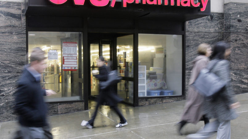 People walk past a CVS pharmacy in downtown Chicago Tuesday, March 18, 2008. On Tuesday, a settlement was announced in Chicago that Rhode Island-based CVS Caremark Corporation has agreed to pay almost $37 million to the federal government, 23 states and the District of Columbia to settle claims it billed Medicaid programs for a more expensive formulation of an antacid. The investigation began more than five years ago after a suburban Chicago pharmacist alerted authorities. (AP Photo/M. Spencer Green)