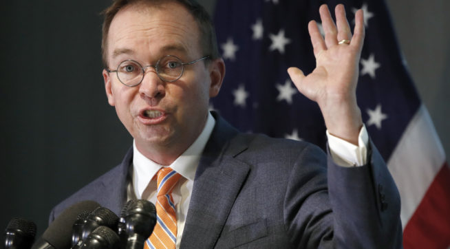 Mick Mulvaney holds up his hand as he speaks during a news conference after his first day as acting director of the Consumer Financial Protection Bureau in Washington, Monday, Nov. 27, 2017. (AP Photo/Jacquelyn Martin)