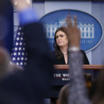 White House press secretary Sarah Huckabee Sanders listens to a reporter's question as other raise their hands to ask a question, during a press briefing at the White House, Tuesday, Dec. 12, 2017, in Washington. (AP Photo/Alex Brandon)