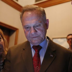 U.S. Senate candidate Roy Moore, center, looks at election returns with staff during an election-night watch party at the RSA activity center, Tuesday, Dec. 12, 2017, in Montgomery, Ala. (AP Photo/Brynn Anderson)