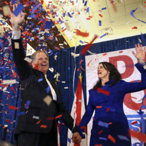 Democratic candidate for U.S. Senate Doug Jones and his wife Louise wave to supporters before speaking during an election-night watch party Tuesday, Dec. 12, 2017, in Birmingham , Ala. Jones is facing Republican Roy Moore. (AP Photo/John Bazemore)