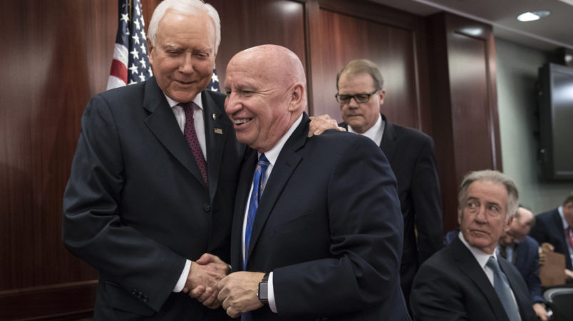 House Ways and Means Committee Chairman Kevin Brady, R-Texas, center, embraces Senate Finance Committee Chairman Orrin Hatch, R-Utah, left, as House and Senate conferees after GOP leaders announced they have forged an agreement on a sweeping overhaul of the nation's tax laws, on Capitol Hill in Washington, Wednesday, Dec. 13, 2017. Rep. Richard Neal, D-Mass., ranking member of the House Ways and Means Committee, looks on at far right. Democrats objected to the bill and asked that a final vote be delayed until Senator-elect Doug Jones of Alabama is seated. (AP Photo/J. Scott Applewhite)