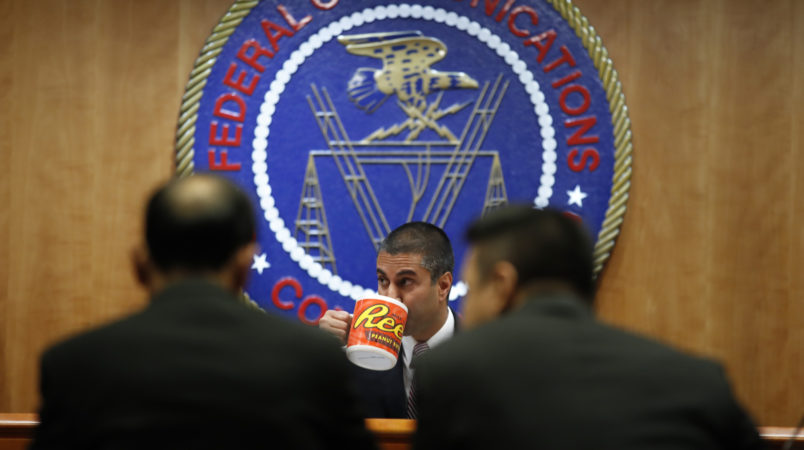 Federal Communications Commission (FCC) Chairman Ajit Pai takes a drink from a mug during introductions during an FCC meeting where they will vote on net neutrality, Thursday, Dec. 14, 2017, in Washington. (AP Photo/Jacquelyn Martin)