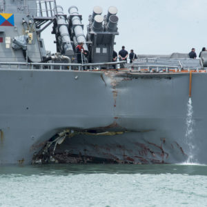 170821-N-OU129-022CHANGI NAVAL BASE, REPUBLIC OF SINGAPORE – Damage to the portside is visible as the Guided-missile destroyer USS John S. McCain (DDG 56) steers towards Changi Naval Base, Republic of Singapore, following a collision with the merchant vessel Alnic MC while underway east of the Straits of Malacca and Singapore on Aug. 21. Significant damage to the hull resulted in flooding to nearby compartments, including crew berthing, machinery, and communications rooms. Damage control efforts by the crew halted further flooding. The incident will be investigated. (U.S. Navy photo by Mass Communication Specialist 2nd Class Joshua Fulton/Released)