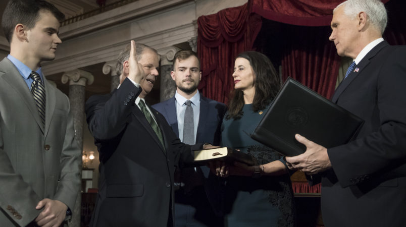 Doug Jones, second from left, the first Alabama Democrat elected to the Senate in a quarter century, is administered the oath of office by Vice President Mike Pence as his wife Louise holds the Bible, joined at far left by their son Christopher Jones, and son Carson Jones, center, during a ceremonial swearing-in at the Capitol in Washington, Wednesday, Jan. 3, 2018. Jones, 63, will represent one of the most conservative states in the nation and is stressing his desire to work with both parties. Jones defeated Republican Roy Moore in a special election to take the seat once held by Attorney General Jeff Sessions. (AP Photo/J. Scott Applewhite)