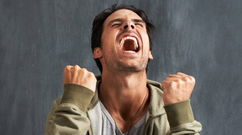 A young man yelling in frustration with his eyes closed