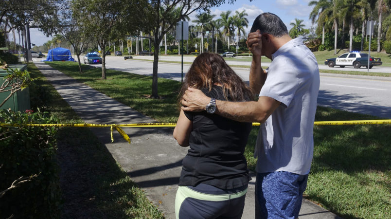 Azra, left, and Unser Khan of Parkland grieve outside of Marjory Stoneman Douglas High School in Parkland, Thursday, Feb. 15, 2018. The family's adult children are both graduates of the school. (Joe Cavaretta/Sun Sentinel/TNS)
