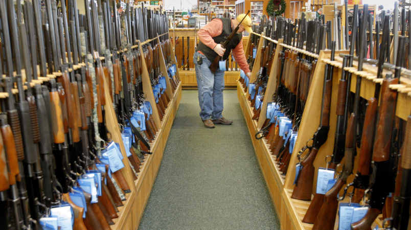 Gregory Rec/Staff Photographer...Don Parizo of Vermont looks over hunting rifles at Kittery Trading Post in Kittery on Wednesday, November 19, 2008.