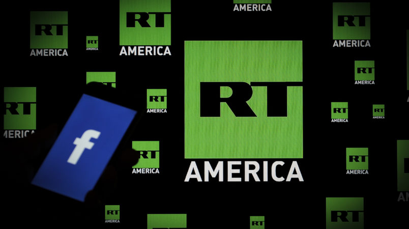 A Facebook logo is seen on a portable device with the logo of Russia Today (RT) news channel in the background in this photo illustration on November 15, 2017. (Photo by Jaap Arriens/NurPhoto)