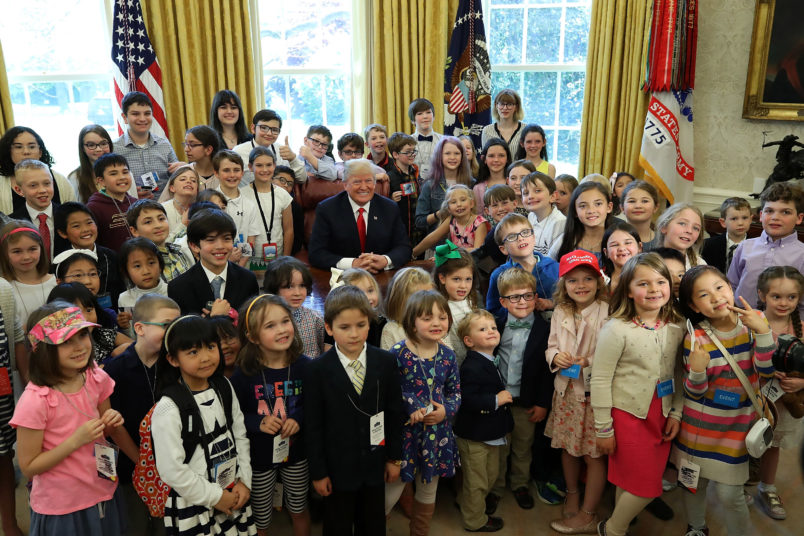 WASHINGTON DC- APRIL 26 U.S. President Donald Trump is surrounded by the children of members of the media during Take Your Child To Work Day in the Oval Office
