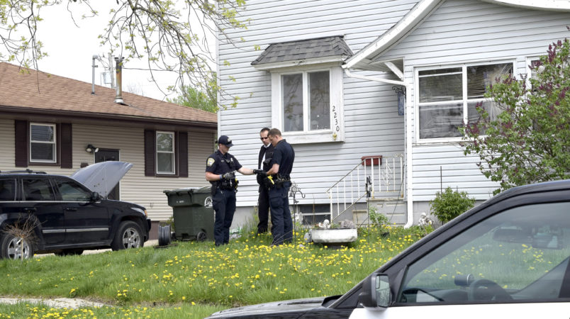 Fort Dodge Police officers Matt Weir, left, Larry Hedlund and Jacob Naatz investigate an accidental shooting, Wednesday, May 9, 2018, in Fort Dodge, Iowa. Richard Remme, of Fort Dodge, told police he was playing with his dog, Balew, on the couch and tossed the dog off his lap. He says when the pit bull-Labrador mix bounded back up, he must have disabled the safety on the gun in his belly band and stepped on the trigger causing the gun to fire and strike Remme in the leg. (Joe Sutter/The Messenger via AP)