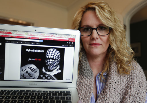 ** HOLD FOR STORY BY RAPHAEL SATTER ** Angela Rickett poses with a screen shot of a message she received from a group claiming to be Islamic State supporters in Bloomington, Ind., Monday, April 9, 2018. Russian spies masquerading as Islamic State supporters threatened outspoken U.S. Army spouses, The Associated Press found, in an operation that presaged the infamous chaos campaign of Russian social media trolls during the American election.(AP Photo/Michael Conroy)
