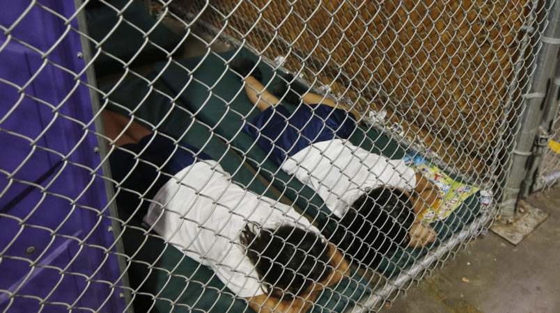 Two female detainees sleep in a holding cell, as the children are separated by age group and gender, as hundreds of mostly Central American immigrant children are being processed and held at the U.S. Customs and Border Protection Nogales Placement Center on Wednesday, June 18, 2014, in Nogales, Ariz.  CPB provided media tours Wednesday of two locations in Brownsville, Texas, and Nogales, that have been central to processing the more than 47,000 unaccompanied children who have entered the country illegally since Oct. 1. (AP Photo/Ross D. Franklin, Pool)