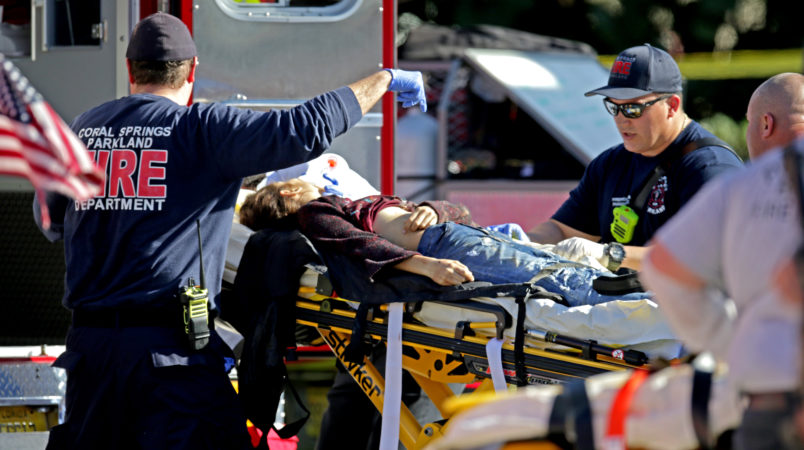 Medical personnel tend to a victim outside of Stoneman Douglas High School in Parkland, Fla., after a shooting on Wednesday, Feb. 14, 2018. (John McCall/Sun Sentinel/TNS)