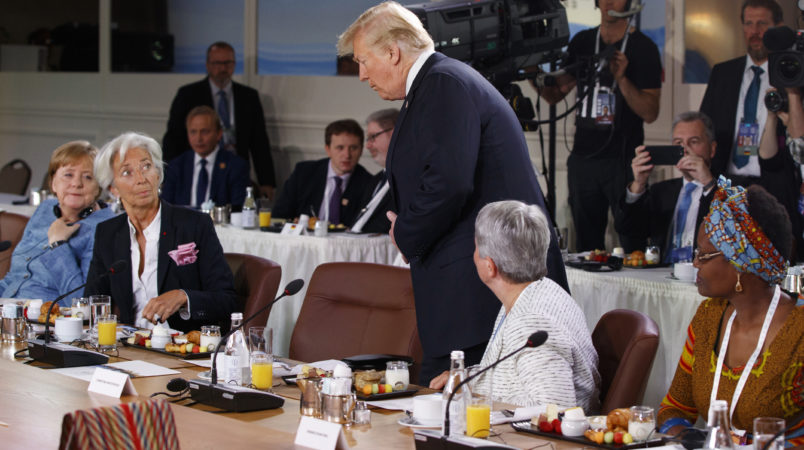 President Donald Trump arrives for a Gender Equality Advisory Council breakfast during the G-7 summit, Saturday, June 9, 2018, in Charlevoix, Canada. From left, German Chancellor Angela Merkel, IMF Managing Director Christine Lagarde, Trump, Christine Whitecross, and Winnie Byanyima. (AP Photo/Evan Vucci)