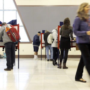 """PORTLAND, ME - NOVEMBER 7: Sue Vittner, right, walks her completed ballot to the scanning booth at the Merrill Auditorium voting station Tuesday morning. Turnout at the station has been """"pretty good,"""" according to Election Warden Carol . By 8:20 a.m., the site had processed ballots from 95 voters, which Morrissette estimated was already three times as many voters who cast ballots at the same station during the May election. (Staff photo by Ben McCanna/Staff Photographer)"""