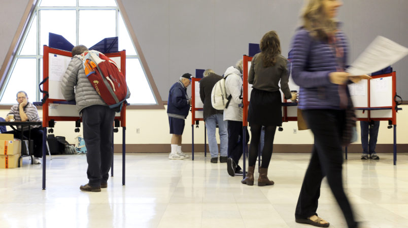 "PORTLAND, ME - NOVEMBER 7: Sue Vittner, right, walks her completed ballot to the scanning booth at the Merrill Auditorium voting station Tuesday morning. Turnout at the station has been ""pretty good,"" according to Election Warden Carol . By 8:20 a.m., the site had processed ballots from 95 voters, which Morrissette estimated was already three times as many voters who cast ballots at the same station during the May election. (Staff photo by Ben McCanna/Staff Photographer)"