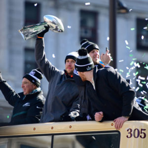 PHILADELPHIA, PA - FEBRUARY 08: (L-R) Team owner Jeffrey Lurie, with quarterbacks Nick Foles #9, Nate Sudfeld #7 and Carson Wentz #11 of the Philadelphia Eagles, acknowledge fans as Foles hoists the Vince Lombardi Trophy atop a parade bus during festivities on February 8, 2018 in Philadelphia, Pennsylvania. The city celebrated the Philadelphia Eagles' Super Bowl LII championship with a victory parade. (Photo by Corey Perrine/Getty Images)